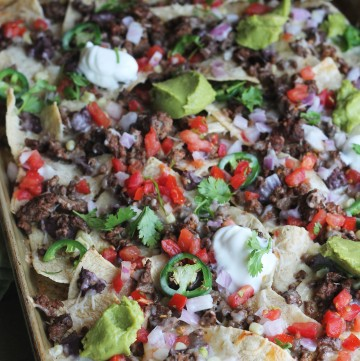 Sheet Pan Beef Nachos loaded with cheese, tomatoes, jalapenos, beans, corn, and queso