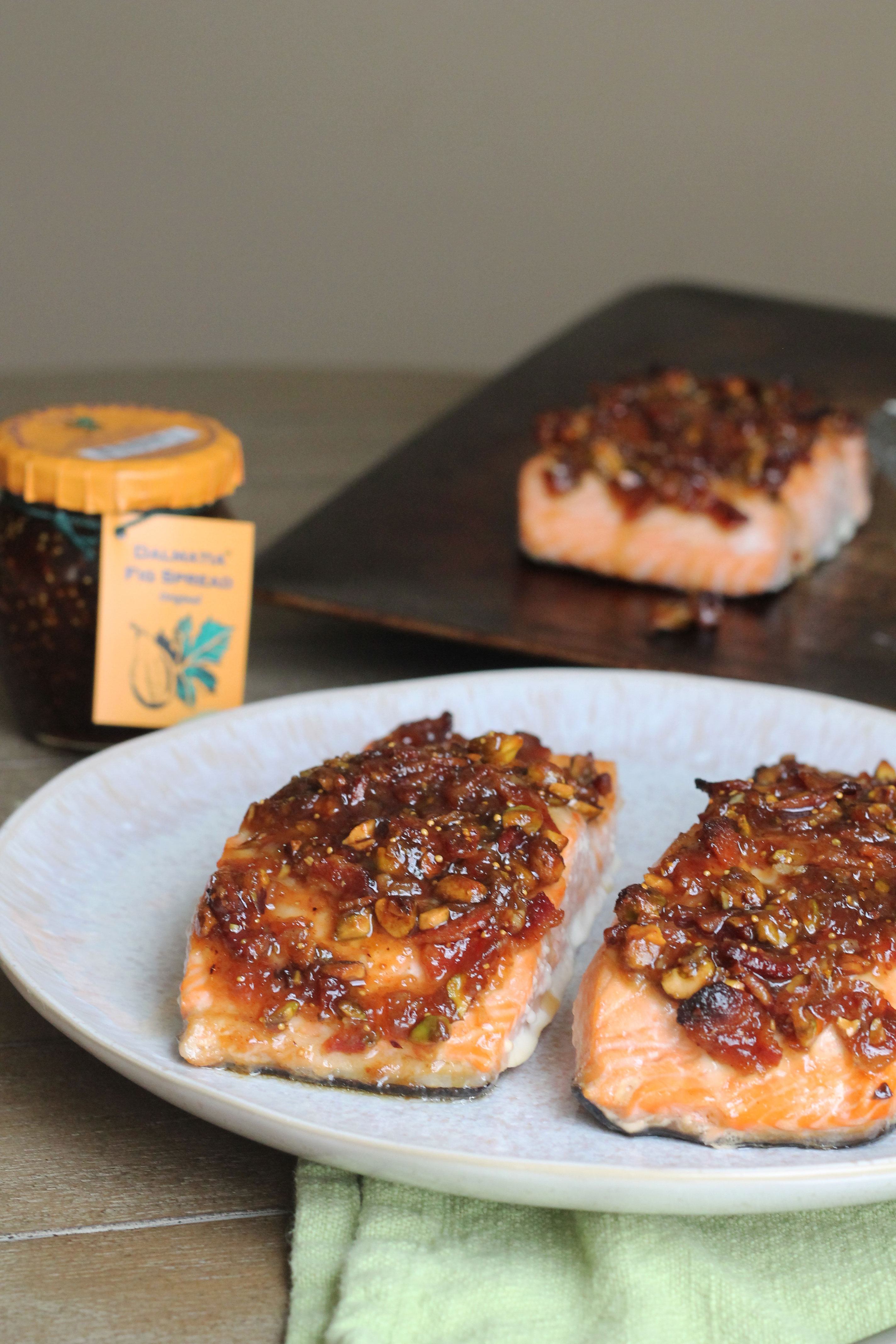 Salmon topped with fig jam, pistachios, and bacon